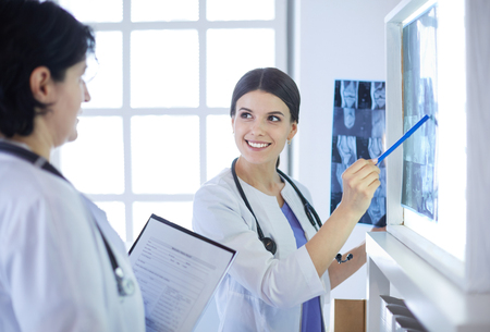 Dos doctores sonrientes apuntando a radiografías en una sala de consulta de un hospital