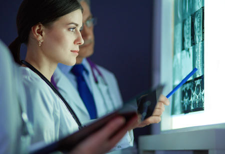 Group of doctors examining x-rays in a clinic, thinking of a diagnosis Stock Photo