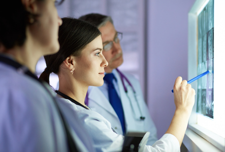 Groupe de médecins examinant les rayons X dans une clinique, pensant à un diagnostic Banque d'images