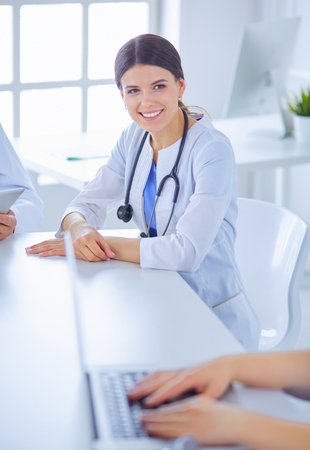 Smiling doctor using a laptop working with her colleagues in a bright hospital room Stock Photo