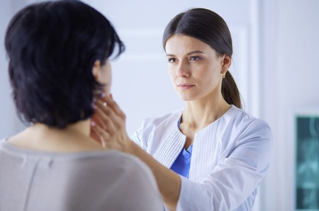 A serious female doctor examining a patients lymph nodes 写真素材 - 121046699