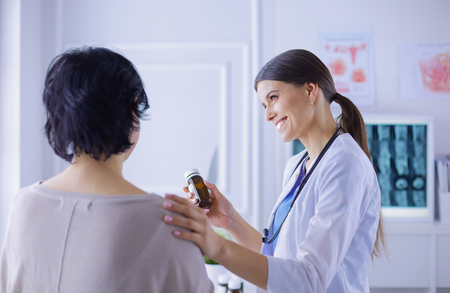 Beautiful female doctor explaining medical treatment to a patient, holding a bottle of medicaments