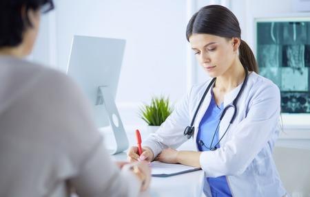 Medico e paziente che discutono di problemi medici in un ambulatorio ospedaliero. Doc che compila un modulo per i pazienti