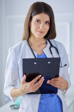 Female doctor standing with a folder in her hands at hospital, smiling at the camera