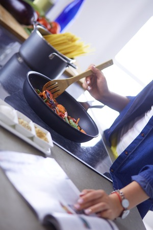 Young woman in the kitchen preparing a food.