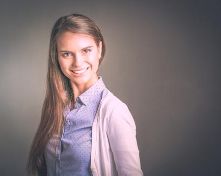 Portrait d'une femme d'affaires sur fond sombre. Femme souriante.