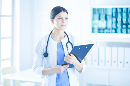 Young smiling female doctor with stethoscope holding a folder at a hospitals consulting room