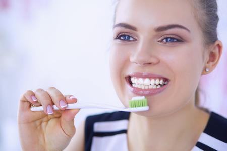 Młoda ładna dziewczyna utrzymanie higieny jamy ustnej szczoteczką do zębów. Zdjęcie Seryjne