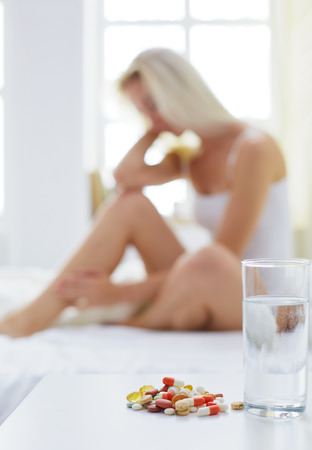 Young beautiful woman with pills sitting on bed in bedroom Stock Photo
