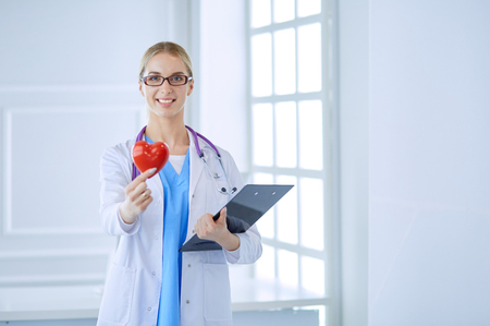 Female doctor with the stethoscope holding heart
