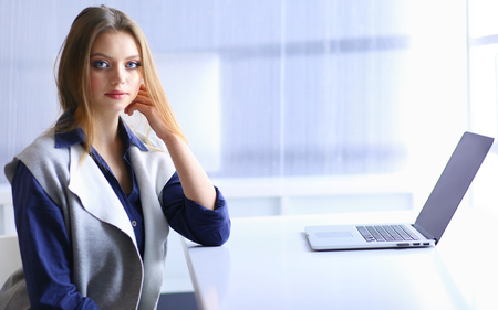 Young confident businesswoman working at office desk and typing with a laptop