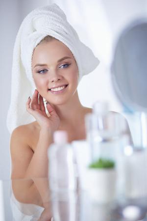 Jeune femme en peignoir à la recherche dans le miroir de la salle de bain Banque d'images