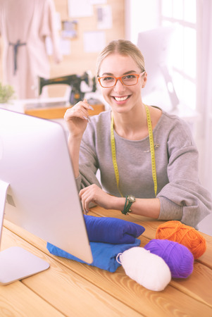 A portrait of a young designer woman using a laptop and smiling,clothes hanged as background 写真素材