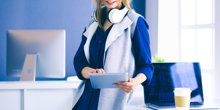 Young businesswoman standing in front of a table in the office Stock Photo