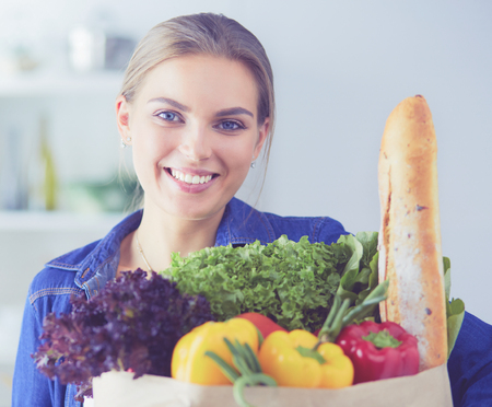 Young woman holding grocery shopping bag with vegetables .Standing in the kitchen Stok Fotoğraf