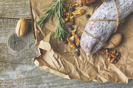 French salami and walnuts on craft paper on wooden background