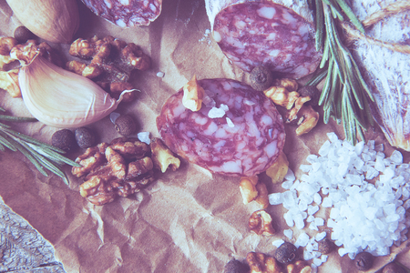 Italian salami wih sea salt, rosemary, garlic and nuts on paper. Rustic style. Top view.