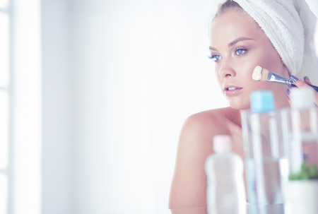 A picture of a young woman applying face powder in the bathroom Banque d'images - 124803090