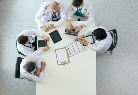 Medical team sitting and discussing at table, top view Foto de archivo - 124803215