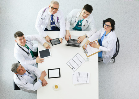 Medical team sitting and discussing at table, top view Foto de archivo - 124803216