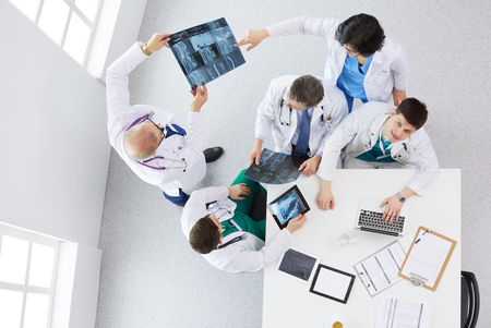 Medical team sitting and discussing at table, top view Foto de archivo - 124803218