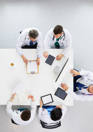 Medical team sitting and discussing at table, top view Foto de archivo - 124803219