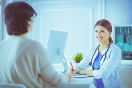 Doctor and patient discussing medical problems in a hospital consulting room. Doc filling in a patients form 写真素材
