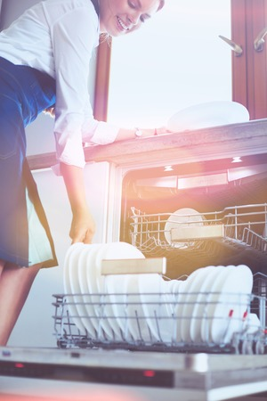 Dishwasher. Young woman in the Kitchen doing Housework. Wash-up Stock Photo