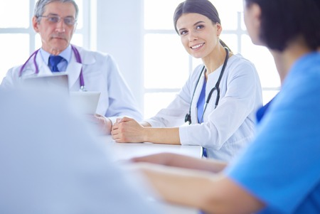 Serious medical team discussing patients case in a bright office