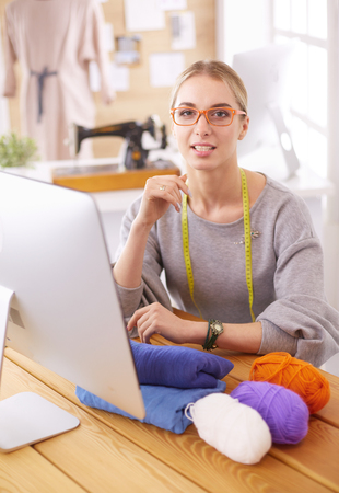 Fashion designer woman working in studio, sitting at thhe desk Stock Photo