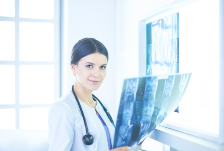Young female doctor with stethoscope examining X-ray at doctors office Stock Photo