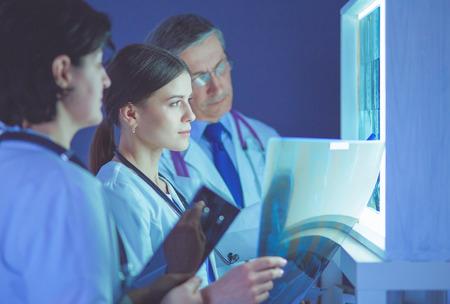Grupo de médicos examinando radiografías en una clínica, pensando en un diagnóstico
