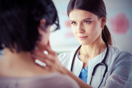 A serious female doctor examining a patients lymph nodes Stock fotó