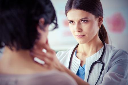 Eine ernsthafte Ärztin untersucht die Lymphknoten eines Patienten patients Standard-Bild