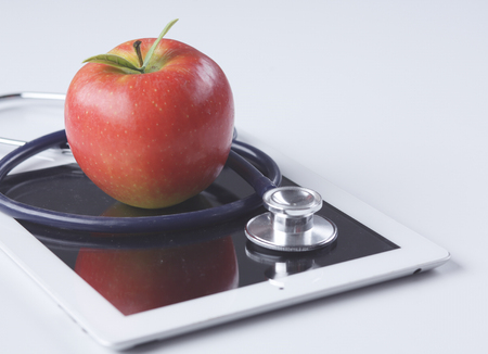 Medical stethoscope and red apple lying on a tablet isolated on white background.