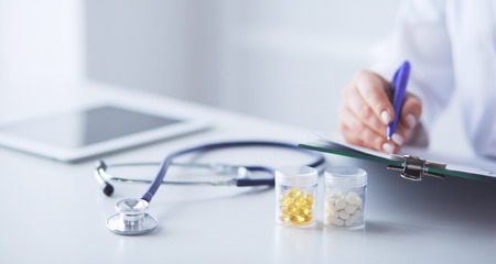 Stetoscopio sdraiato sulla scrivania di vetro con computer portatile a sfondo medico occupato. Concetto di medicina o farmacia. Strumenti medici al tavolo di lavoro del medico