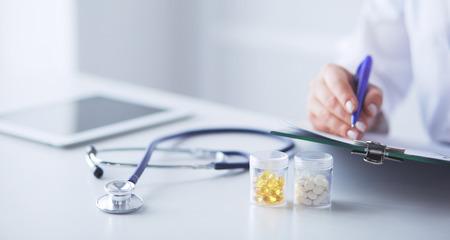 Stetoskop leżący na szklanym biurku z laptopem na tle zajęty lekarz. Koncepcja medycyny lub farmacji. Narzędzia medyczne przy stole roboczym lekarza