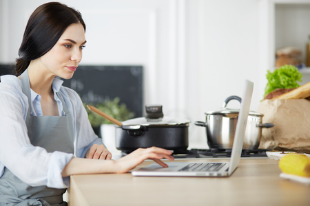 Young woman using a tablet computer to cook in her kitchen.