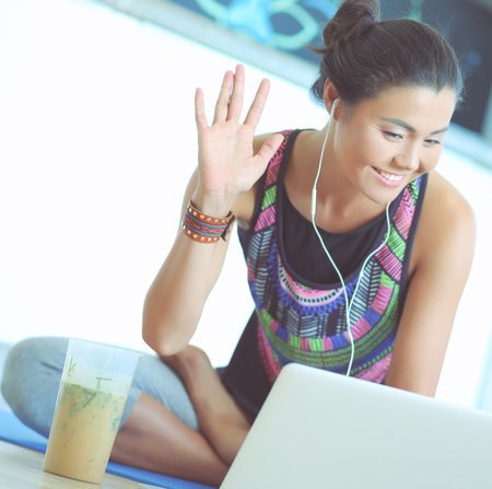 Sporty smiling woman using laptop in bright room. Woman. Lifestyle