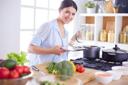 Mujer joven de pie junto a la estufa en la cocina