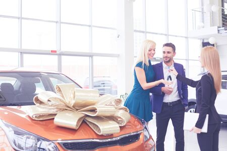 Beautiful cheerful woman holding up car keys, embracing her husband after buying new car