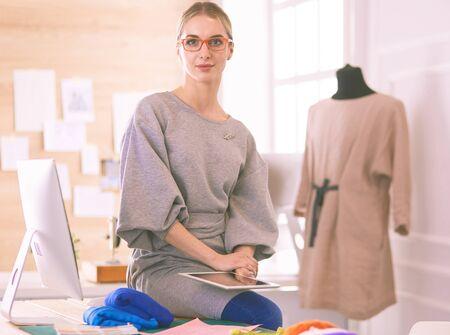 Beautiful fashion woman designer standing in studio
