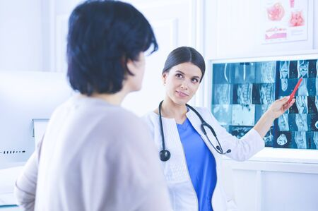 Female medicine doctor explains to patient diagnosis pointing with pen to x-ray picture. Patient listening carefully doctor recommendations.