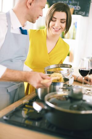 Attractive couple in love cooking and opens the wine in the kitchen while they cook dinner for a romantic evening 免版税图像