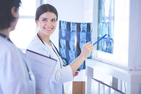 Two smiling doctors pointing at x-rays in a hospital consulting room Foto de archivo