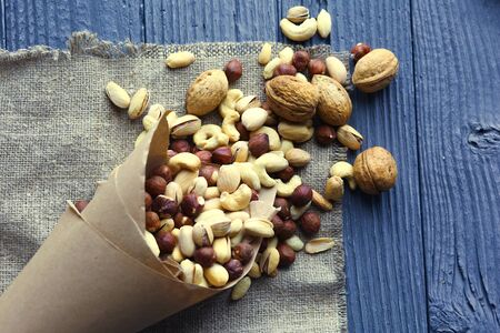 Mix of different nuts in a paper cup against the background.