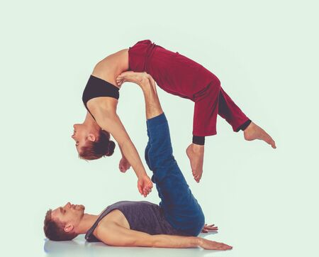Young athletic couple practicing yoga. Balancing in pair.