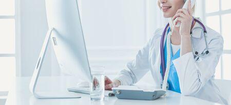 Femme médecin ayant un appel téléphonique au cabinet médical Banque d'images