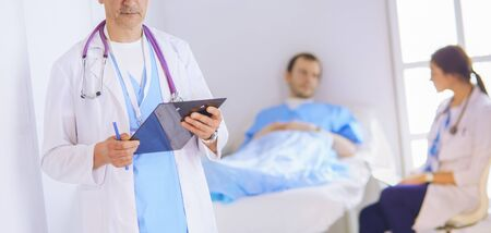Doctor holding folder in front of a patient and a doctor Stock Photo