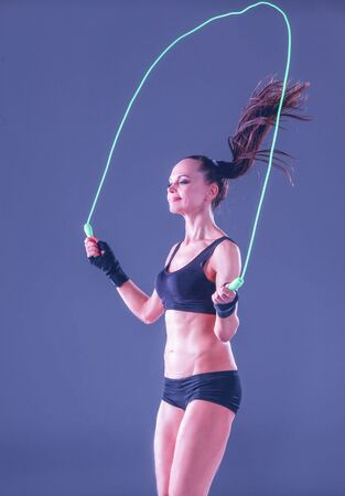 Muscular young woman standing on gray background. Muscular young woman. beautiful girl jumping rope